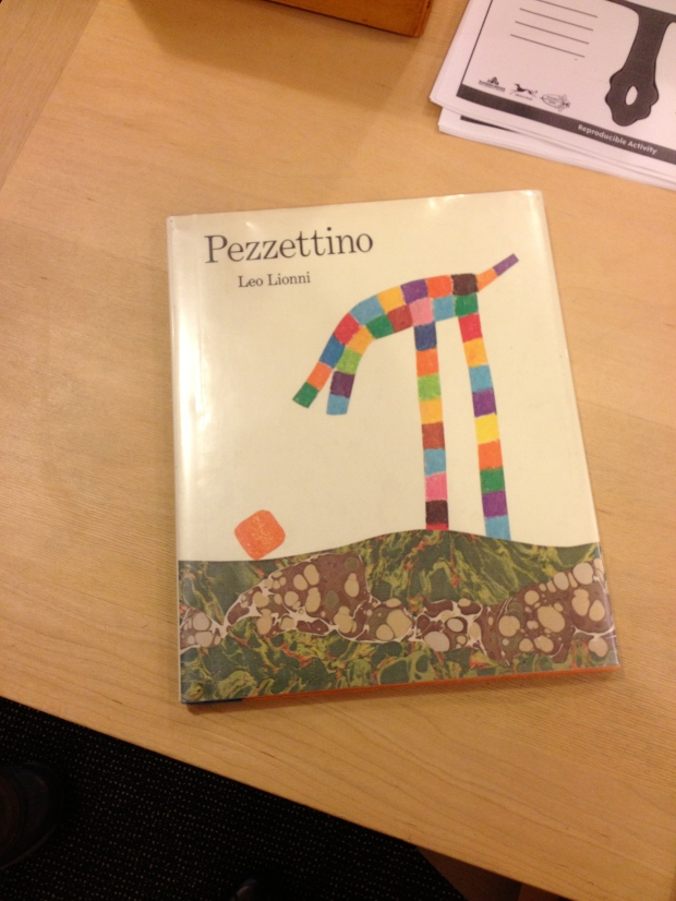 "Library Book on Display: Pezzentino (Italian for ""little piece"") is a small orange cube that searches for his place in the world."